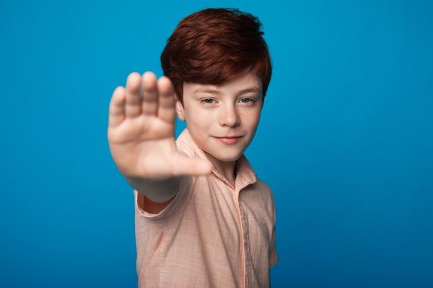 Крупным планом фото улыбающегося мальчика с рыжими волосами и веснушками, жестикулирующего знак остановки на синей стене