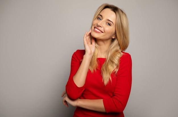 Крупным планом фото потрясающей женщины в красном наряде, которая позирует впереди, держа правую руку возле подбородка и сложив левую руку, улыбается и смотрит в камеру.