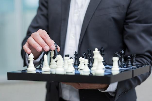 Крупным планом фото успешного бизнесмена, держащего шахматную доску и делающего ход