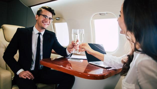 비즈니스 클래스 비행기에서 비행기를 타면서 동료와 샴페인 피리를 부딪치고 있는 성공한 남자의 클로즈업 사진.