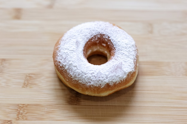 Крупным планом фото пончика из сахарной пудры на деревянном столе.