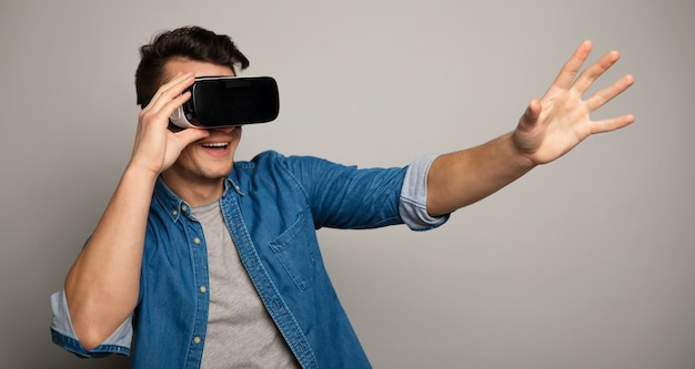 カメラの前で手を広げているvrメガネで驚いた男の写真をクローズアップ。