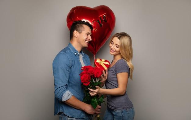 Крупным планом фото сладкой парочки, которые празднуют день святого валентина, даря друг другу подарки и от счастья улыбаются.