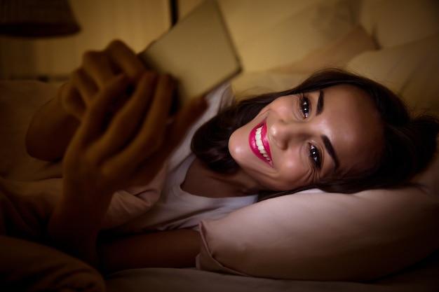 Фото крупным планом уставшей девушки, лежащей в постели под одеялом, у которой проблемы со сном из-за своей интернет-зависимости.