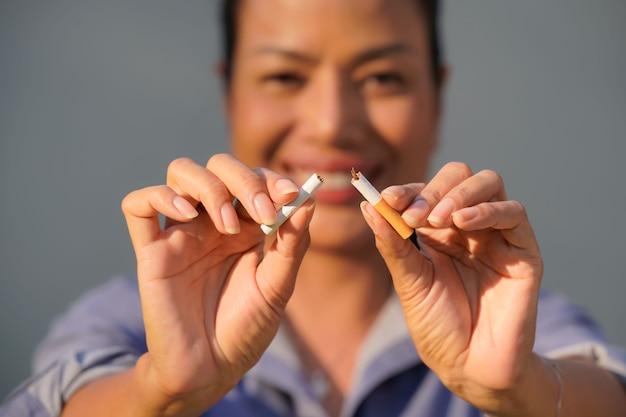 Крупным планом - женщина, уничтожающая сигареты, во всемирный день без табака, 31 мая, бросьте курить.
