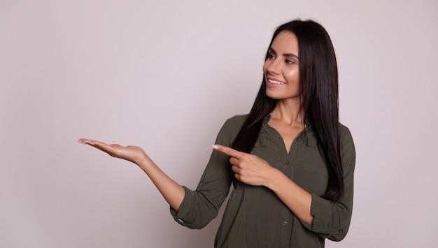 카메라를 바라보며 왼손으로 엄지손가락을 치켜들고 오른손에 무언가를 들고 있는 척 활짝 웃는 멋진 검은 머리 소녀의 클로즈업 사진.