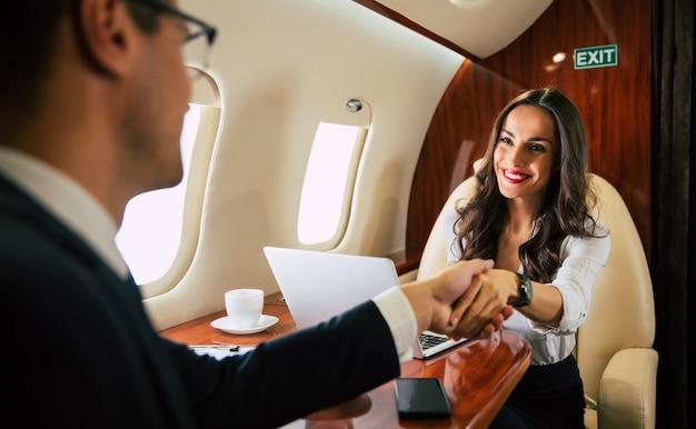 멋진 여성이 비즈니스 파트너와 함께 일등석 비행기에 탑승하면서 악수하는 모습을 클로즈업한 사진입니다.