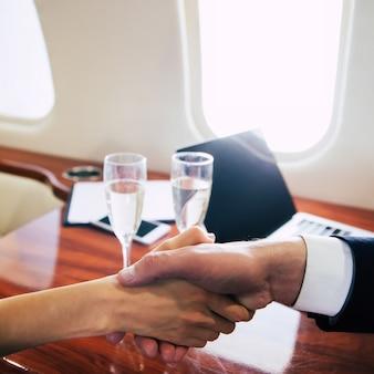 一流の飛行機のボードで彼と一緒に飛行機に乗っている間、彼女のビジネスパートナーと握手している素晴らしい女性のクローズアップ写真。