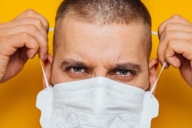 コロナウイルスの検疫中に医療用フェイスマスクで若いひげを生やした白人男性の写真をクローズアップ。顔の前の部分が少しぼやけています。コロナウイルス、covid-19発生。医師、看護師のコンセプト。