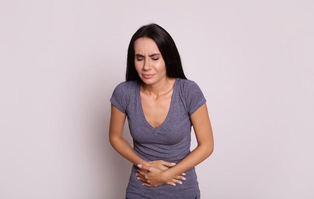 Фотография крупным планом молодой брюнетки, которая держится руками за живот, что указывает на то, что у нее болит живот.