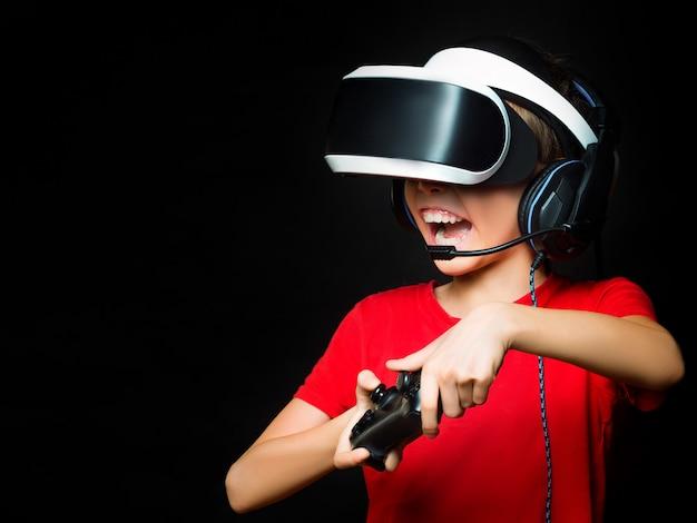 興奮した顔でビデオゲームをプレイするvrの少女の写真をクローズアップ。