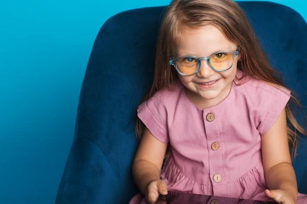 여유 공간 근처의 파란색 벽에 안락 의자에 앉아있는 동안 노란색 안경 앞에서 웃는 어린 소녀의 사진을 닫습니다