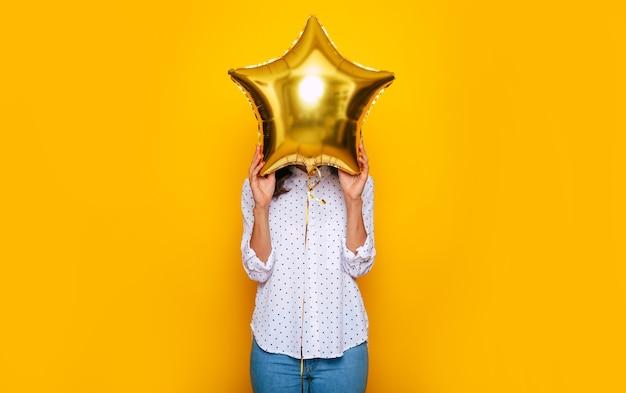 彼女は黄色の背景に分離された星の形をした風船の助けを借りて彼女の顔を覆っている間、若い女の子の写真をクローズアップ