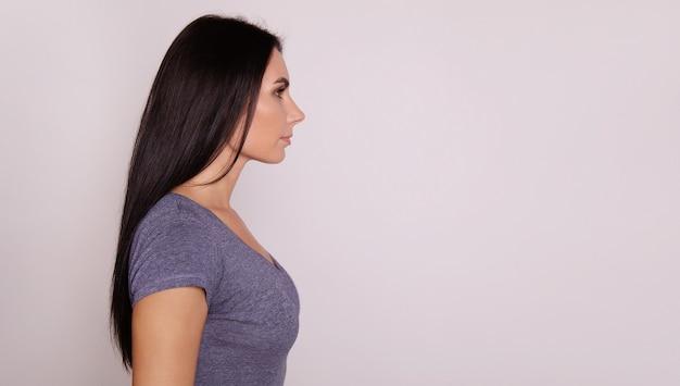 긴 검은 머리를 가진 젊고 사랑스러운 여성의 클로즈업 사진, 프로필에서 포즈를 취하고 그녀가 향하고 있는 방향을 바라보고 있습니다.