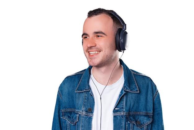 흰색 배경 위에 이어폰에서 음악을 듣고 젊은 남자의 사진을 닫습니다.