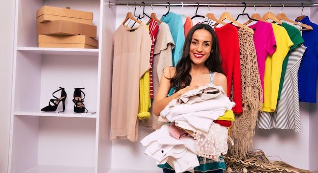 긴 밤색 머리를 가진 완벽한 젊은 여성의 클로즈업 사진은 그녀의 구획 옷장 근처에 리넨 더미와 함께 프로필에 서서 웃고 기대하고 있습니다.