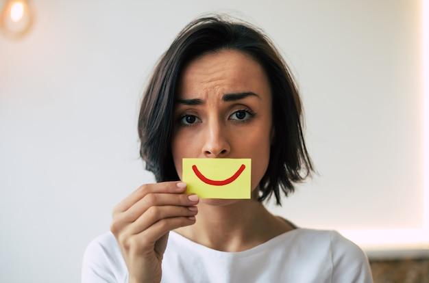 Крупным планом фото грустной молодой девушки, которая грустно смотрит в камеру, держа открытку с улыбкой возле своего рта.