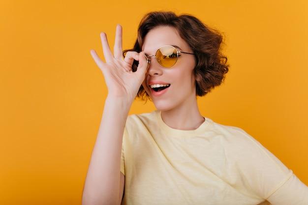 노란색 선글라스에 사랑스러운 창백한 소녀의 근접 사진