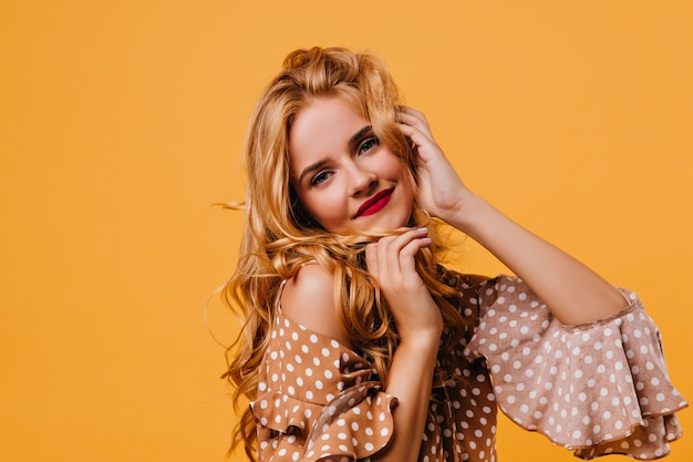 빈티지 갈색 드레스에 사랑스러운 여자의 근접 사진. 노란색 벽에 포즈 유행 블라우스에 매력적인 곱슬 소녀.