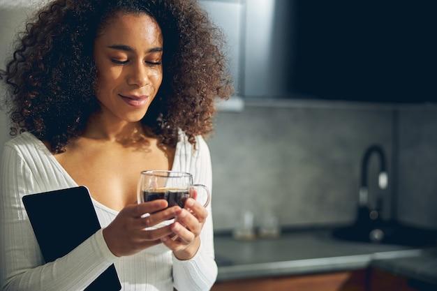 부엌에 서서 커피를 들고 꿈을 꾸는 아프리카 계 미국인 여성의 사진을 닫습니다