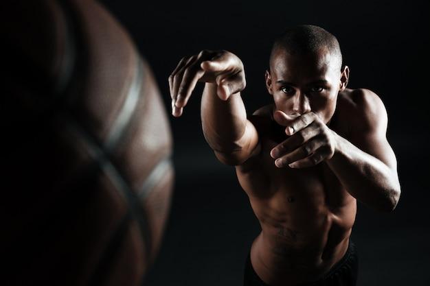 Фото конца-вверх шарика афро-американского баскетболиста бросая,