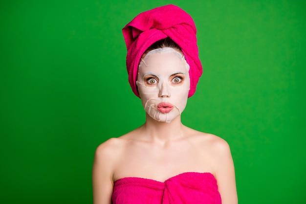 Крупным планом фото изумленной женщины, применяющей коллагеновую маску на лице, не может шевелиться, изолированный зеленый цвет фона