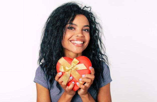 Крупным планом фото удивительной африканской этнической девушки с длинными черными волосами и блестящими глазами, которая находится над луной, держа в руках красную коробку в форме сердца с золотой лентой