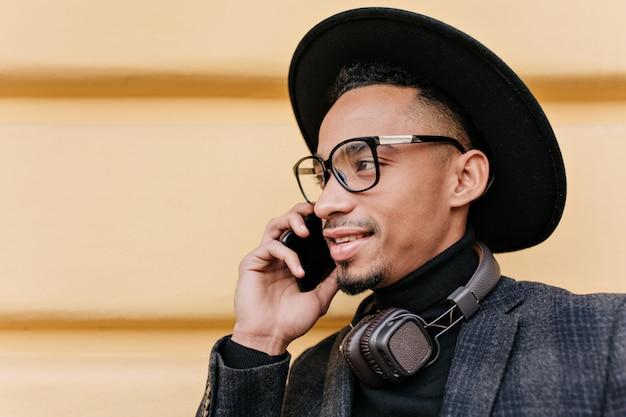 검은 모자에 미국 남성 모델의 클로즈업 사진. 아침에 거리에서 전화 통화하는 잘 생긴 아프리카 남자의 야외 초상화.