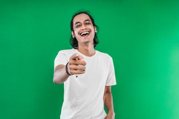 緑の壁に孤立して笑っている長い黒髪のアジア人男性のクローズアップ写真