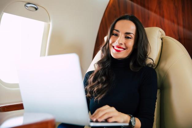 飛行中にラップトップで何かを入力している間、微笑んでいる長い栗の髪の魅力的な女の子のクローズアップ写真。