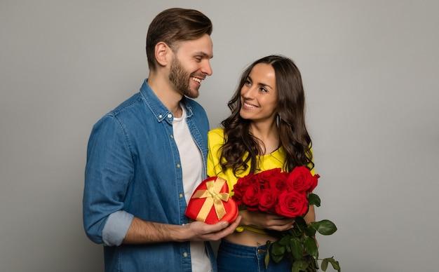 彼のゴージャスなガールフレンドがバラの花束を受け取った後、彼に微笑んでいる間、彼の手に赤い箱を持っている魅力的な男性の写真をクローズアップ。