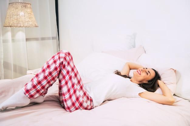 분홍색 침대 시트로 침대에서 푹 자고 있는 매우 아름다운 소녀의 클로즈업 사진.