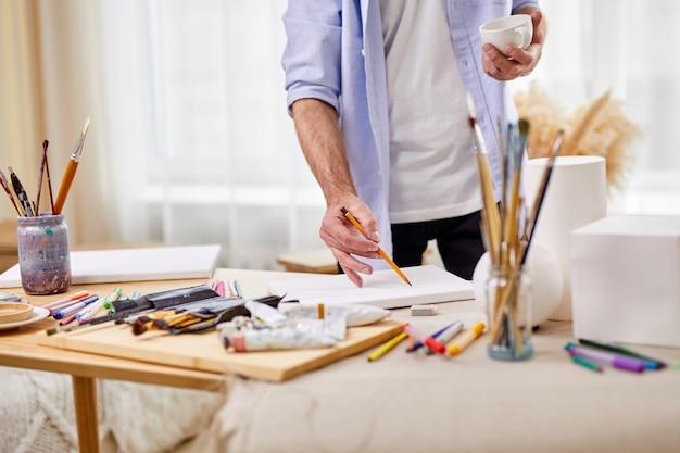시트에 연필로 그리는 아티스트 남자의 근접 사진, 테이블에 그림을 그리는 다른 도구