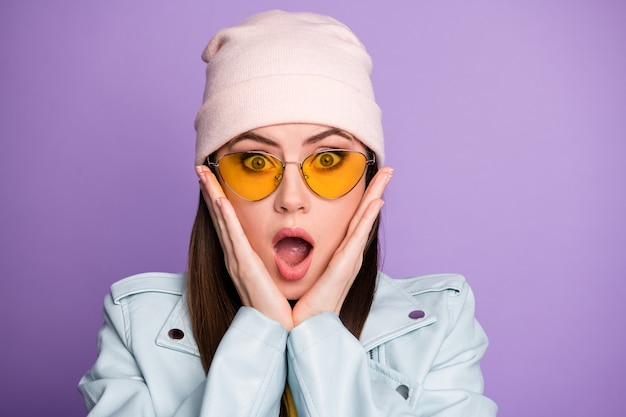 놀란 소녀의 클로즈업 사진은 끔찍한 코로나바이러스 참신한 터치 손 얼굴이 보라색 배경 위에 격리된 좋은 옷을 입는다는 소리를 듣는다