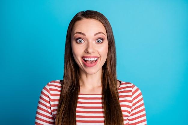 驚いた女の子のクローズアップ写真は信じられないほどの季節の販売ノベルティ感動シャウトウェアが青い色の背景の上に分離された良い気分のプルオーバーに見えるのを聞く