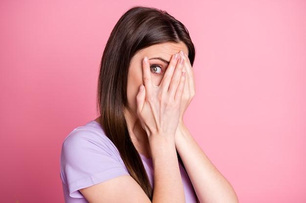 놀란 겁 먹은 소녀가 휴식을 취하는 tv 공포 시리즈를 보고 있는 클로즈업 사진 닫기 손 얼굴은 분홍색 배경 위에 격리된 멋진 옷을 입는다