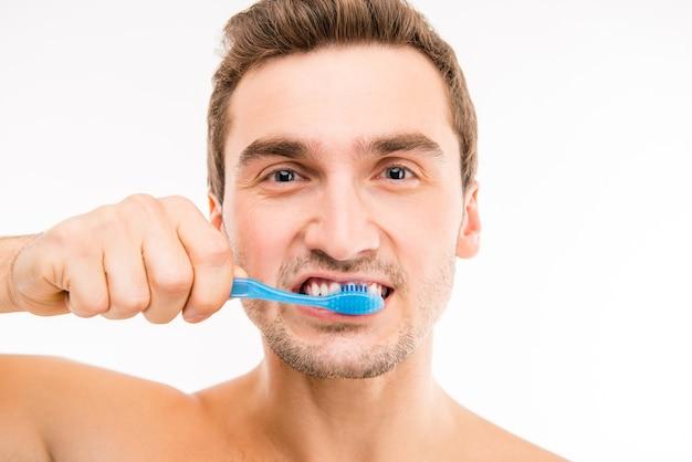 彼の歯を磨く魅力的な男性の写真を閉じる