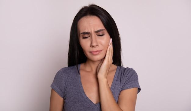 歯痛のように右腕で頬を抱えて右上を向いている魅力的な悲しい少女のクローズアップ写真