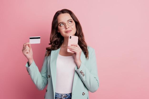 Sms 스마트 폰을 입력하는 매력적인 웃는 소녀의 사진을 닫습니다 신용 카드를 제시하는 빈 공간을 찾습니다