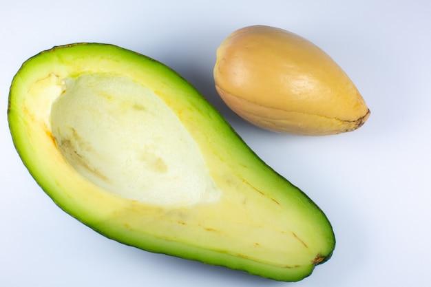 흰색 바탕에 아보카도 사진을 닫습니다. 건강한 과일은 내부에 씨앗이 있는 반으로 잘리고 거시적입니다.