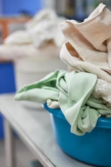 Фото крупным планом тазика с грязной одеждой для стирки в стиральной машине. уборка, стирка, работа по дому, концепция работы по дому.