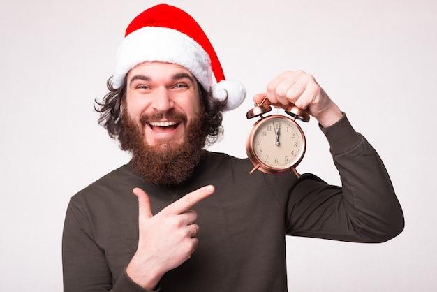 Крупным планом фото бородатого мужчины, указывающего на будильник и ожидающего нового 2021 года