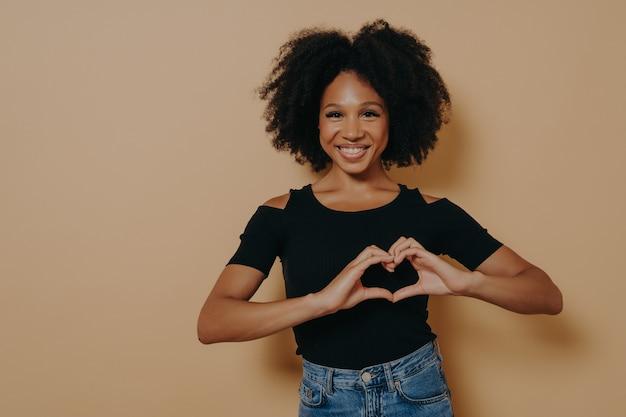 恋人のシンボル、愛のメッセージのジェスチャー、コピースペースでダークベージュのスタジオの背景の上に分離されたカジュアルな黒のtシャツを着て示す美しい驚くべき暗い肌の女性の写真を閉じる