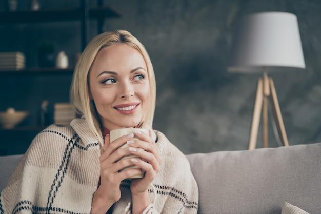 Крупным планом фото красивой блондинки, держащей чашку горячего кофе с напитком, наслаждайся выходными, дома мечтатель, расслабляйся, уютный диван, покрытый одеялом, в гостиной