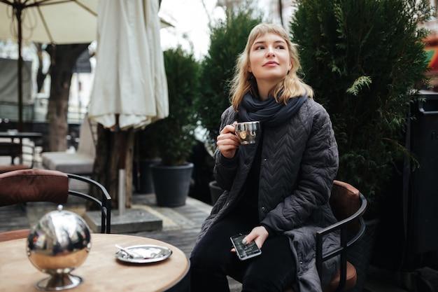 通りのテーブルに座ってコーヒーを飲む美しい女性の写真を閉じる