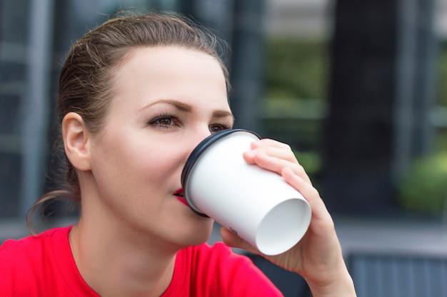Закройте вверх по фото красивой задумчивой заботливой девушки, молодой женщины думая, выпивая, наслаждаясь кофе от одноразового бумажного стаканчика внешнего летнего дня. дама с кофе, чтобы пойти. концепция зависимости от кофеина