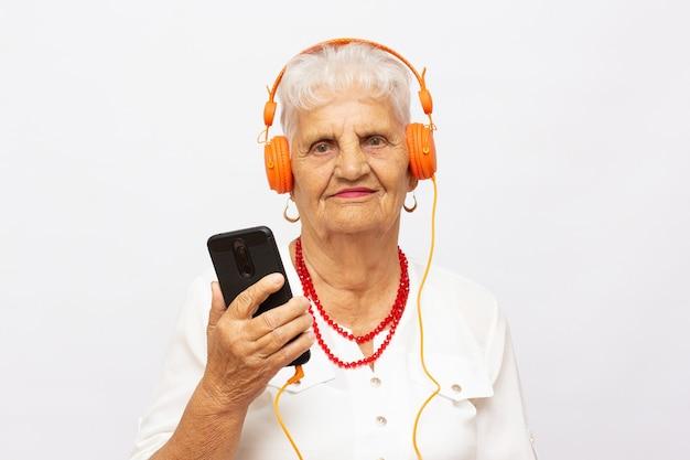 灰色の背景に分離されたヘッドフォンと電話を持つ美しいシニア白人老婆の写真を閉じる