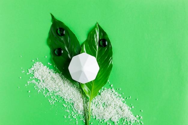 향기로운 목욕 소금과 신선한 녹색 식물 잎으로 아름다운 스파 개념 구성의 사진을 닫습니다