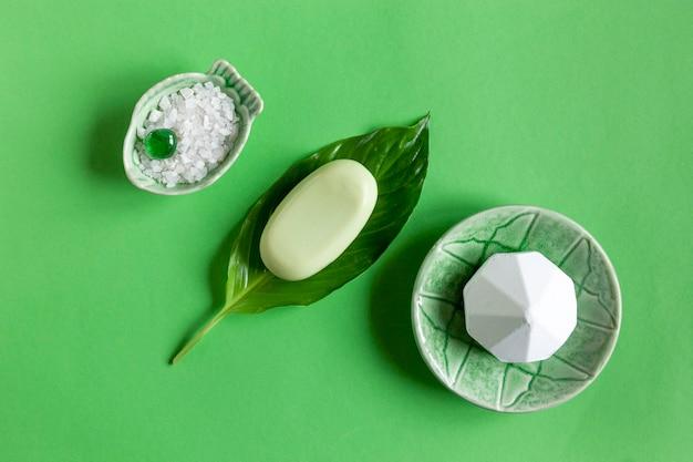 향기로운 목욕 소금, 비누 및 신선한 녹색 식물 잎으로 아름다운 스파 개념 구성의 사진을 닫습니다