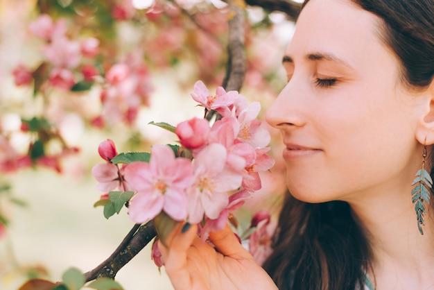 나무에서 좋은 분홍색 꽃 냄새를 맡는 아름다운 여성의 사진을 클로즈업